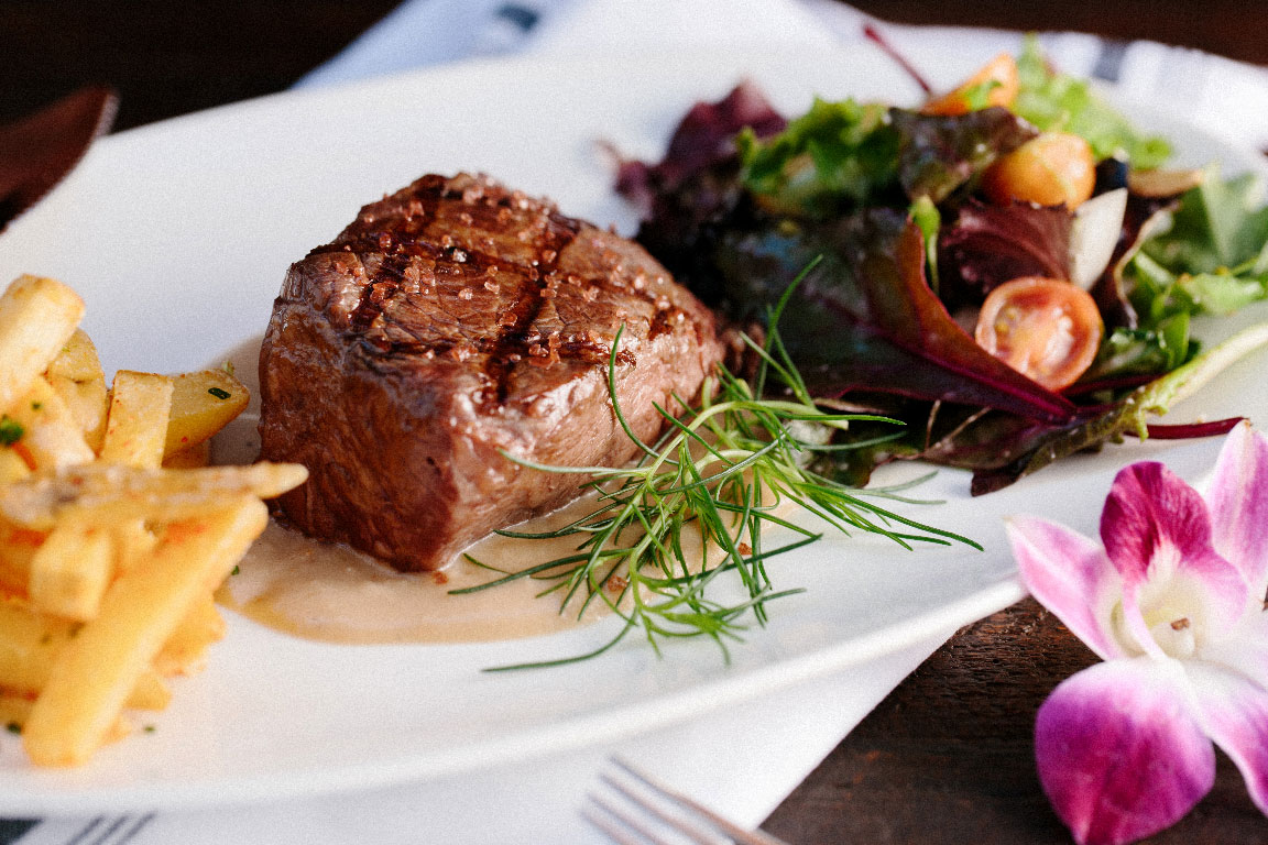 photo of a steak dinner with fries, salad, and a flower