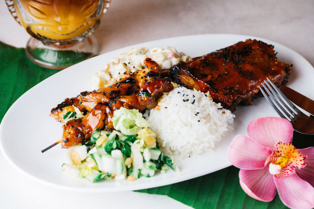 photo of a lunch plate with chicken, rice, a cocktail, and a flower